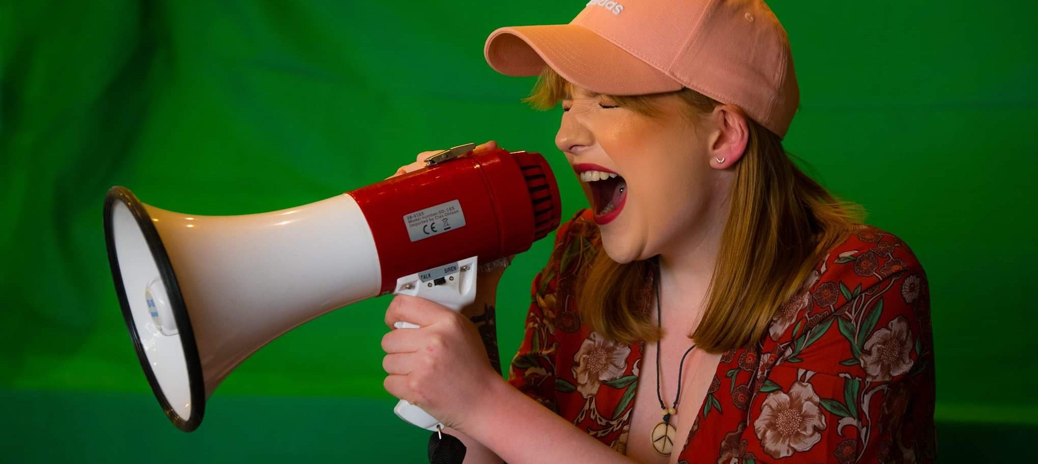 Jodie Langford wearing a pink baseball cap, holding a megaphone up to her mouth and visibly yelling!